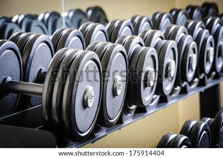 Row of barbells or dumbbells in the gym - stock photo
