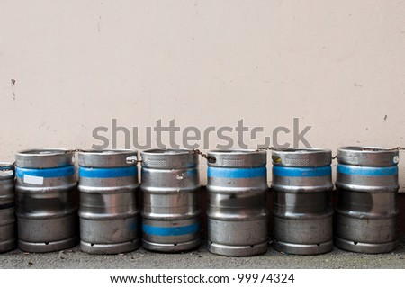 row of beer kegs against a light pink wall (copy-space available) - stock photo