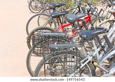 Row of bicycles locked at public bike rack.Rear of bikes lined up.Twin rear carrier wire bike baskets,horseshoe bike lock in foreground.Black knobby tires.Blue padded seats.Reddish concrete pavement.