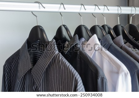 row of black and white shirts hanging in wardrobe