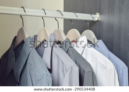 row of black and white shirts hanging in wardrobe - stock photo