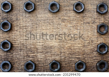 row of black nut in each side on the old cracked wooden background - stock photo