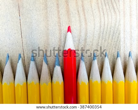 Row of black pencils with one red pencil in middle against wooden background. Out from the crowd. - stock photo