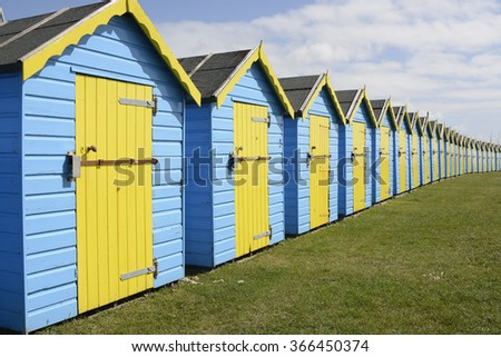 Row of blue and yellow beach huts on the seafront promenade at Bognor Regis in West Sussex, England - stock photo