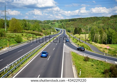 Row of blue cars and black cars entering the asphalt highway between lush forests in the countryside. In the distance the bridge and Electronic toll gate. Sunny day with white clouds in the blue sky. - stock photo