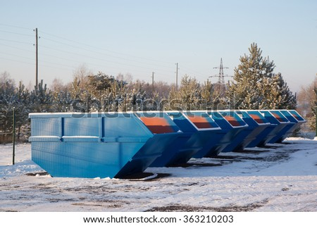 Row of blue large garbage containers at winter day on the open place