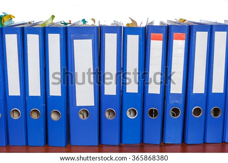 Row of blue office folders with blank labels on desk - stock photo