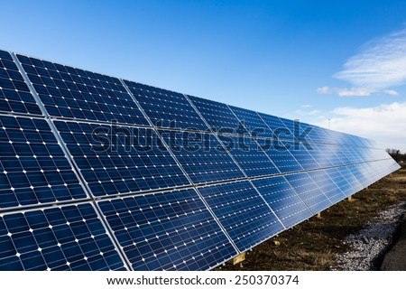 Row of blue photovoltaic solar panels and the sky
