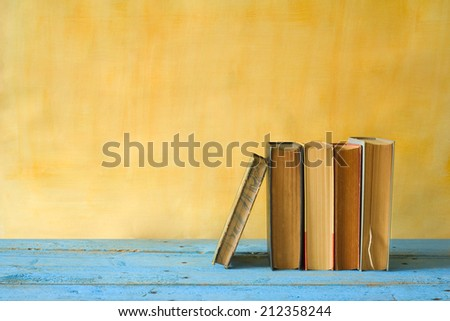 row of books, grungy background, free copy space  - stock photo