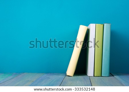 Row of books, grungy blue background, free copy space Vintage old hardback books on wooden shelf on the deck table, no labels, blank spine. Back to school. Education background - stock photo