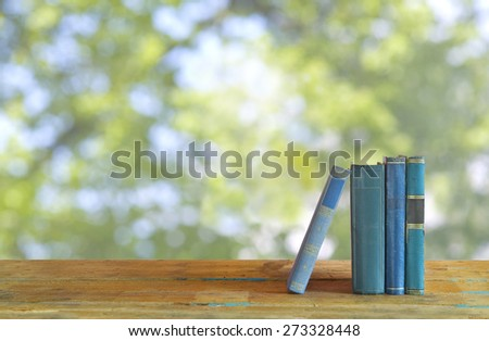 row of books, nature background, free copy space  - stock photo