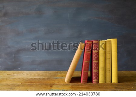row of books, on blackboard background, free copy space - stock photo