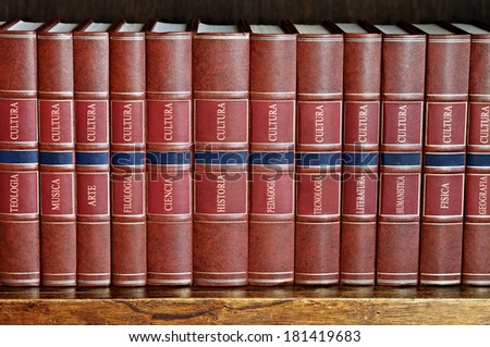 row of books with brown cover on a shelf with titles in Spanish