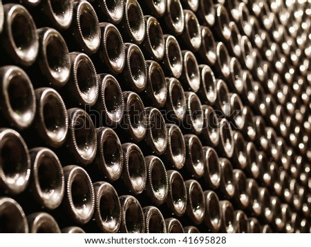 Row of Bordeaux wine bottles stacked in a cellar with shallow depth of field