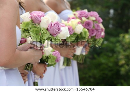 Row of bridesmaids holding bouquets at wedding ceremony - stock photo