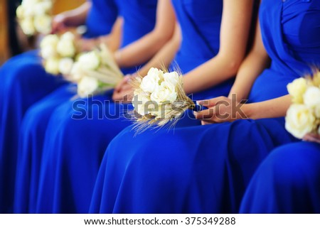 Row of bridesmaids wearing blue dresses holding wedding bouquets at wedding ceremony - stock photo