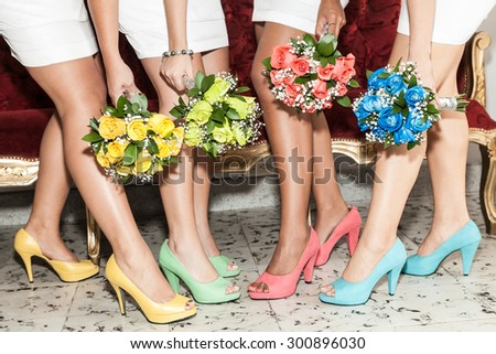 Row of bridesmaids with bouquets of flowers and shoes of different colors - stock photo
