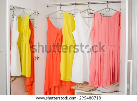 row of bright colorful dress hanging on coat hanger, shoes and handbag in white wardrobe