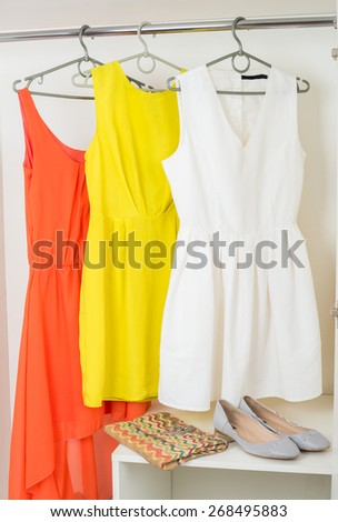 row of  bright colorful female dresses hanging on coat hanger, shoes and handbag in white wardrobe