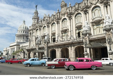 Row of brightly colored vintage American cars stand parked on the street in front of the Galician Palace on Prado Street in central Havana Cuba  - stock photo