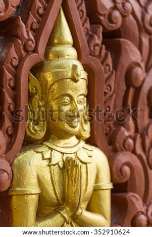 Row of Buddha statues on Buddhist temple wall - stock photo