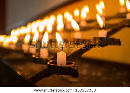 Row of burning candles in the church. Shallow DOF - stock photo