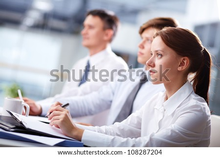 Row of business people attending a seminar and listening closely - stock photo
