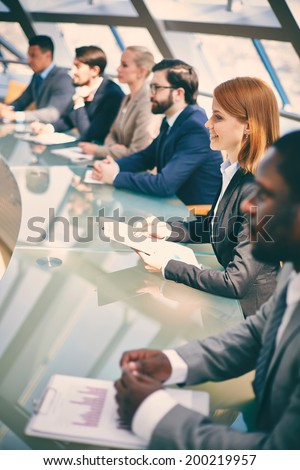 Row of business people listening to presentation at seminar with focus on smiling woman