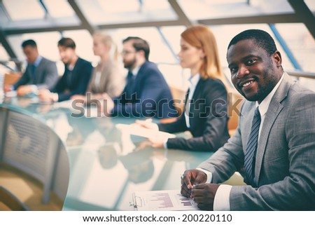 Row of business people listening to presentation at seminar with smiling man on foreground - stock photo