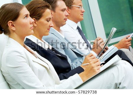 Row of business people writing lecture at conference - stock photo