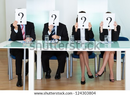 Row of businesspeople with question marks signs in front of their faces - stock photo