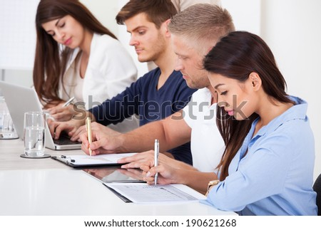 Row of businesspeople working at desk in office - stock photo