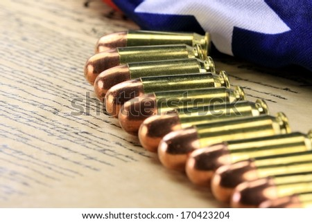 Row of 45 caliber ammunition with US flag in background - stock photo