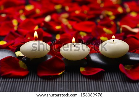 Row of candle with stones and red rose petals on mat - stock photo