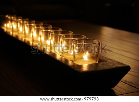 Row of Candles on a Dark Rustic Table - stock photo