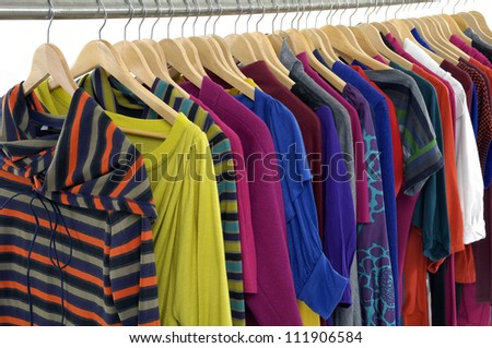 Row of casual clothes of different colors on wooden hangers - stock photo