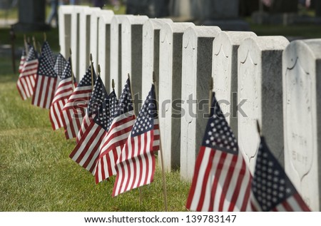 Row of cemetery headstones decorated with American Flags, close up
