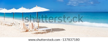 Row of chairs and umbrellas on a beautiful tropical beach at Anguilla, Caribbean - stock photo
