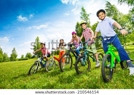 Row of children in colorful helmets holding bikes - stock photo