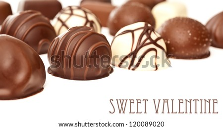Row of chocolate pralines on white background