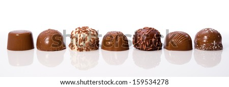 Row of chocolate truffles on white background with reflections - stock photo