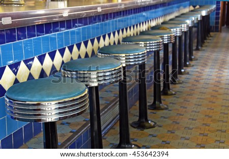 row of chrome and leather barstools in old retro diner - stock photo