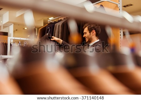 Row of classical men's suits, modern young handsome businessman choosing classical suit in the suit shop in the background - stock photo