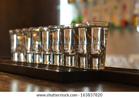 Row of clean shiny glasses lined up on a bar counter in a nightclub ready for the barmen to use to serve alcoholic beverages, oblique row with shallow dof - stock photo