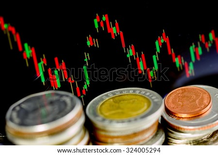 Row of coins and candle graph is represented as down trend in finance market. Focus on graph. - stock photo