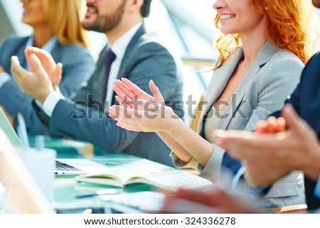 Row of colleagues applauding to speaker at seminar - stock photo