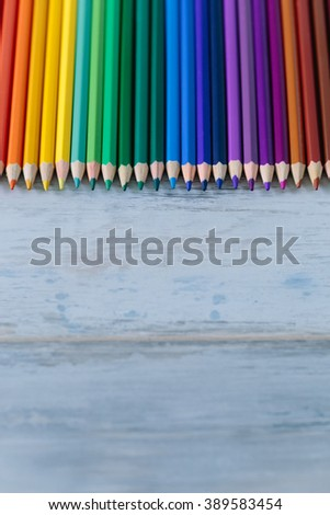 Row of color pencils on the blue vintage wood background copy space - stock photo