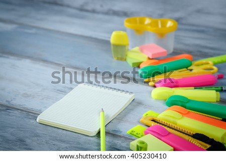 Row of color pens pencils markers and other stationery near the clean notebook on the blue vintage wood background copy space