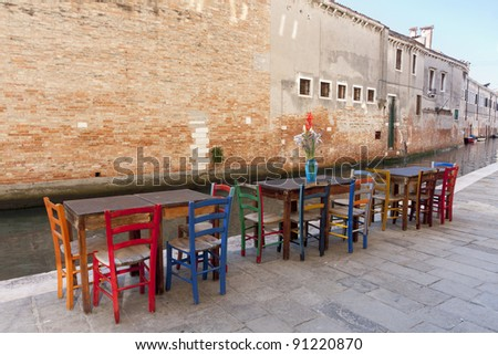 Row of colored chairs and tables  , Venice, Italy.