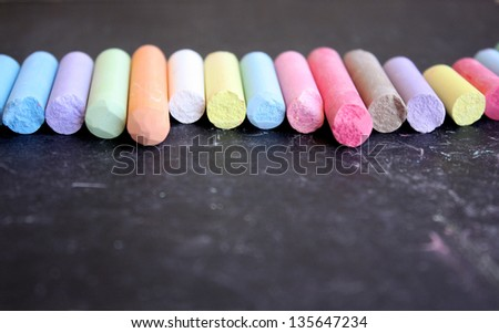 Row of colored chalk on blackboard - stock photo